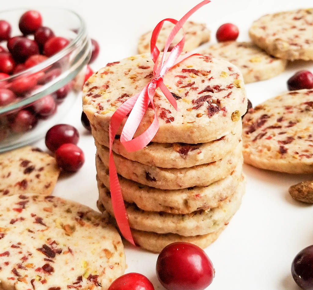 round ginger shortbread cookie with bits of dried cranberries and pistachios stacked and tied with a red ribbon on white surface