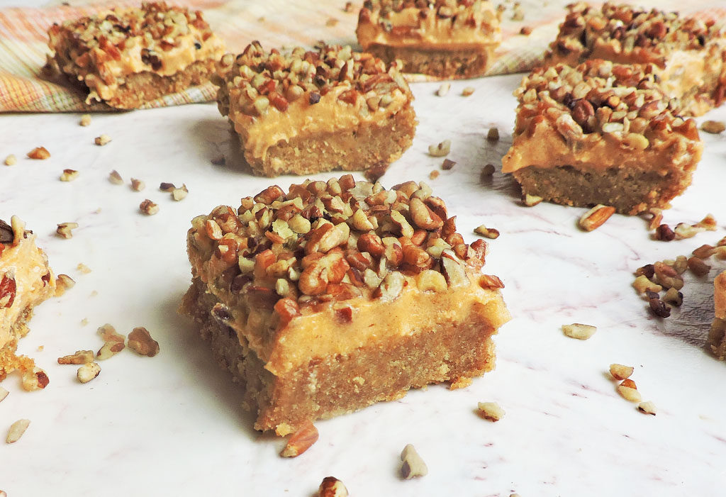 Greek yogurt sweet potato bar with graham cracker crust with pecans on top on white surface