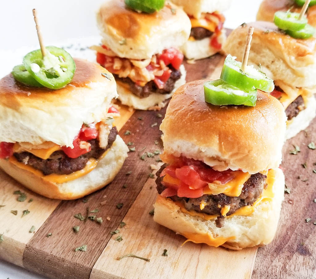 hamburger slicer with american cheese, diced tomatoes, fried onions, topped with fresh jalapenos , on a wooden board