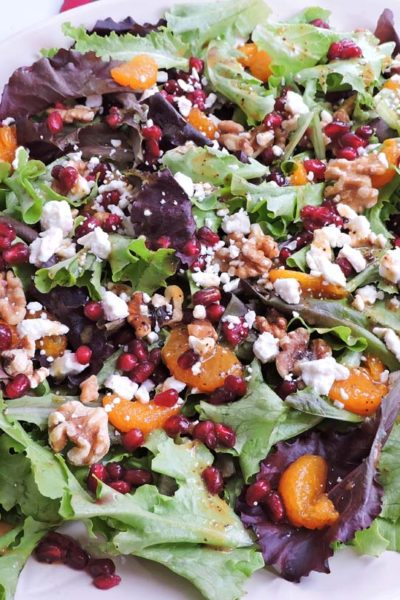 holiday spring mix salad with oranges pomegranate seed walnuts and feta on a white plate christmas