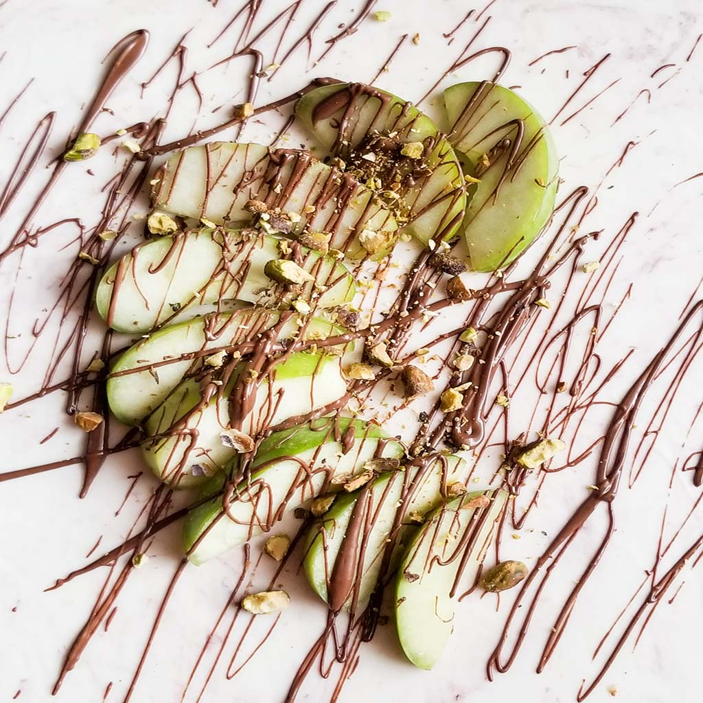sliced green apples with melted chocolate drizzle and pistachios on a white surface