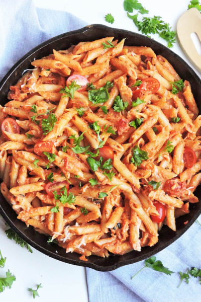 penne pasta with a creamy tomato sauce, served in a cast iron skillet, top with fresh basil