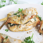 Chicken breast stuffed with cream cheese and spinach, topped with cheese, rosemary and parsley, on a white plate with gold utensils