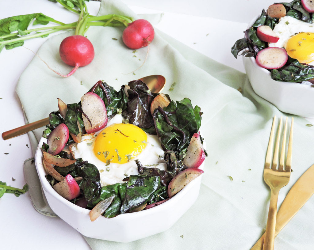 Sauteed Swiss Chard, Radish, and Fried Egg Breakfast in white Bowl, with gold utensils on white surface