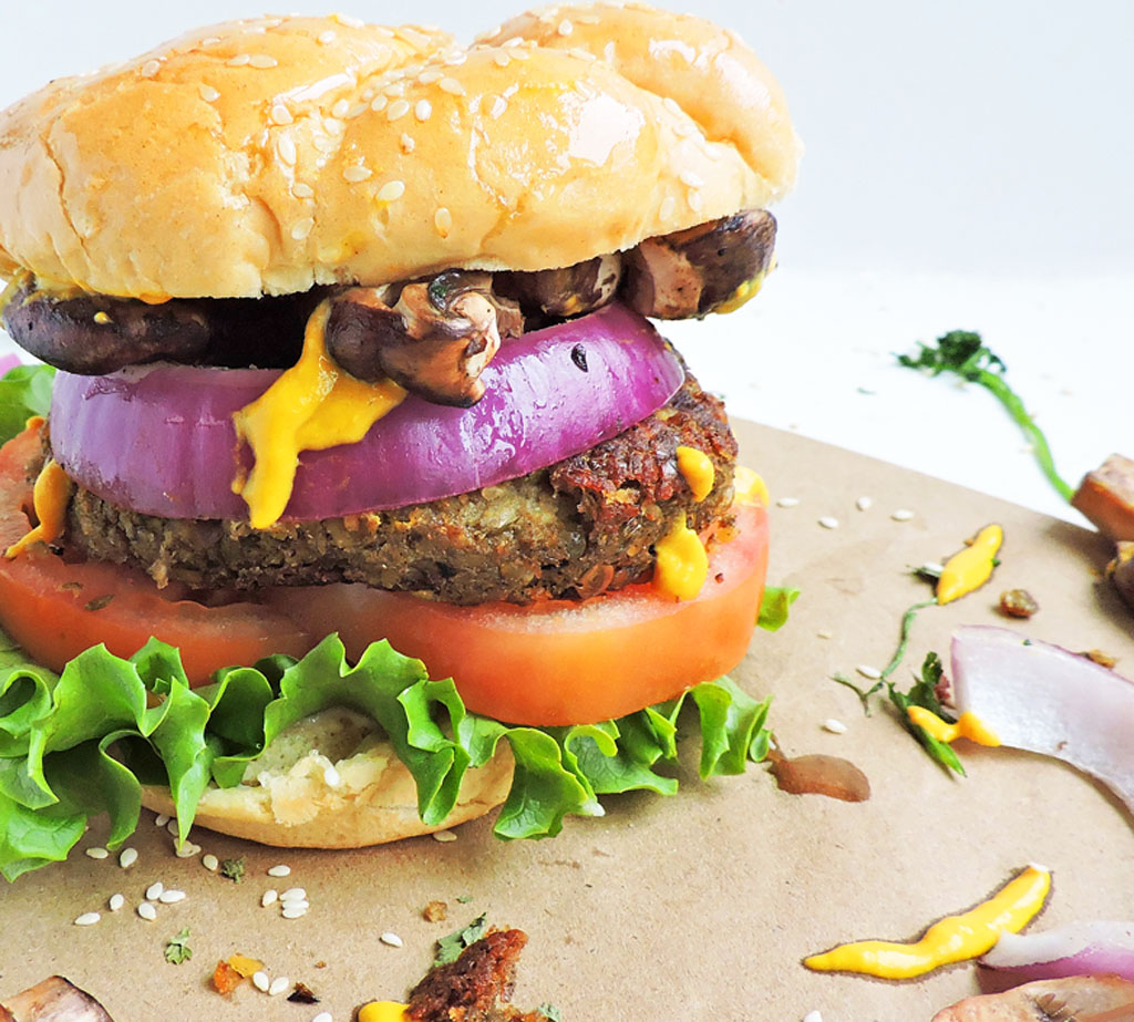 Completely Vegan Lentil Burgers with lettuce, tomatoes, purple onions, mushrooms and mustard on a sesame seed bun, on a white surface