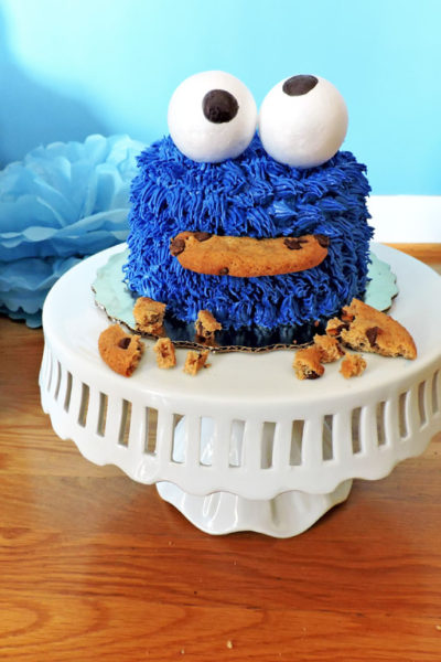 DIY Cookie Monster Smash Cake, with royal blue icing, googly eyes, chocolate chip cookies and balloons