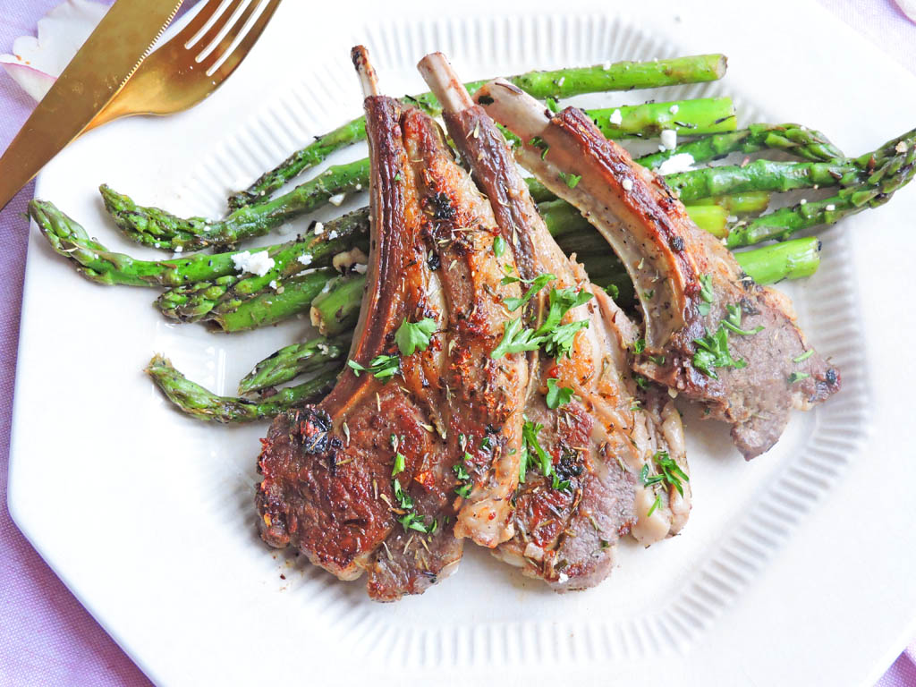 Date Night Herb Crusted Lamb Chops, sprinkled with parsley on top of roasted balsamic asparagus with feta, on a white plate. perfect for Valentine's Day