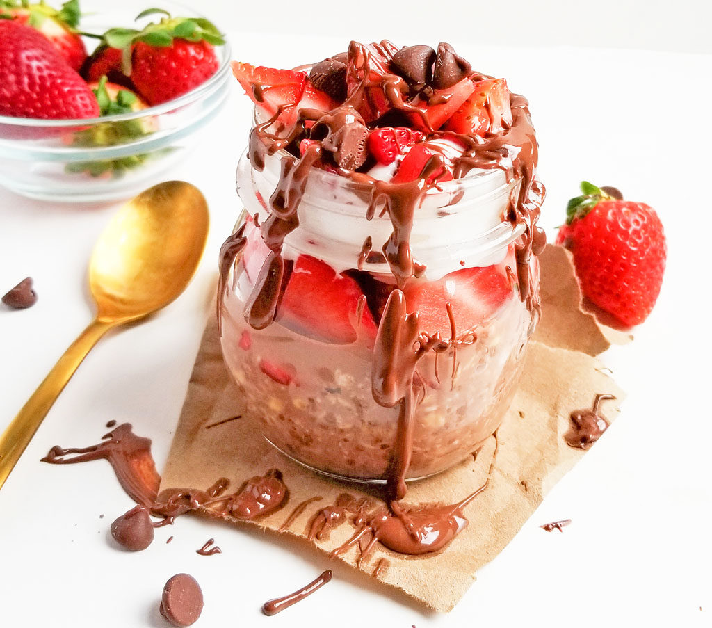 Decadent Chocolate Covered Strawberry Overnight Oats in a jar topped with whipped cream, strawberries, chocolate chips, drizzled with milk chocolate on a white surface
