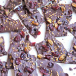 dark chocolate cranberry bark with pistachios, dried cranberries, cacao nibs, and flax seeds on a white surface
