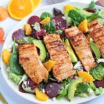 Citrus Flavored Grilled Salmon, placed on top of a bed of Spring salad mix with beets, oranges, and avocado, on a white platter.