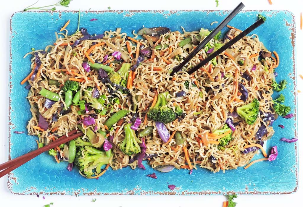 Garlic Ginger Vegetable Ramen Noodle Stir Fry topped with red cabbage, shredded carrots, broccoli, and snap peas; served on a blue platter and chopsticks