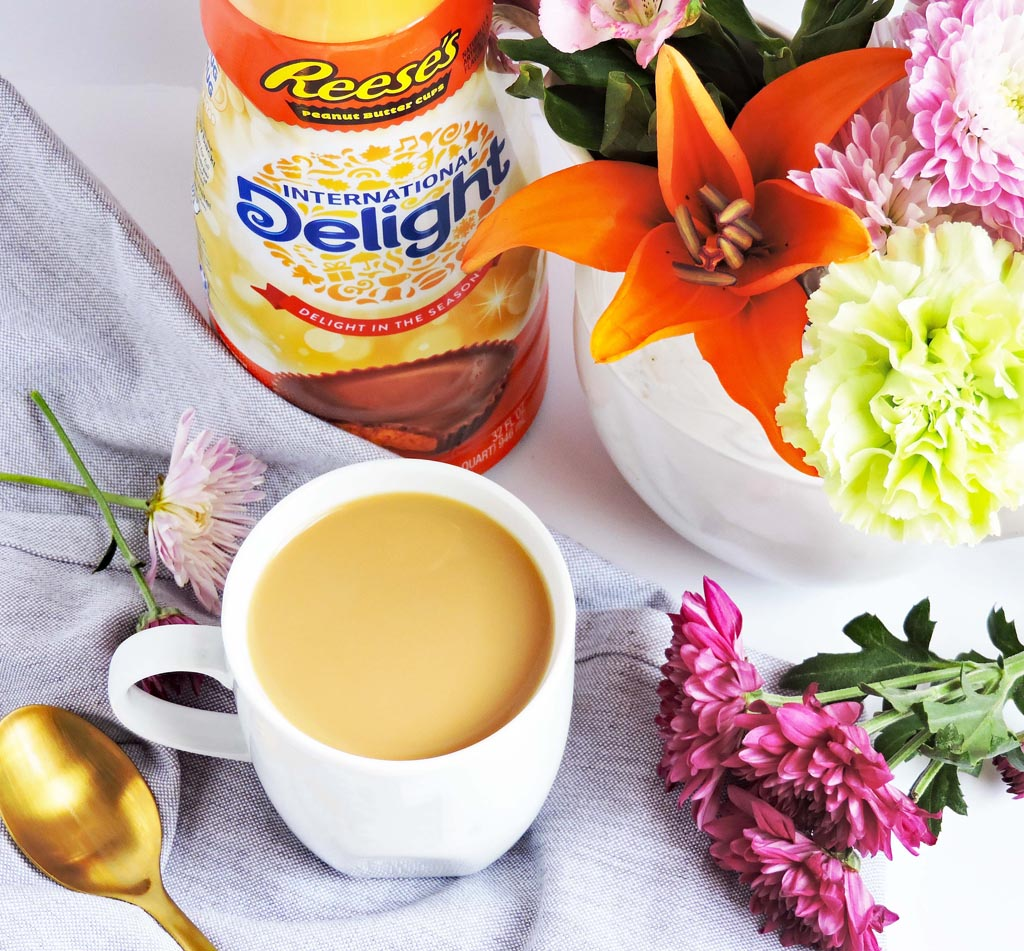 coffee with International Delight Creamer Reese's Cup next to coffee cup and bouquet of Spring flowers