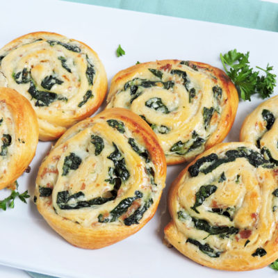 Spinach and Prosciutto Pinwheels made with cream cheese, served on a white plate garnished with parsley