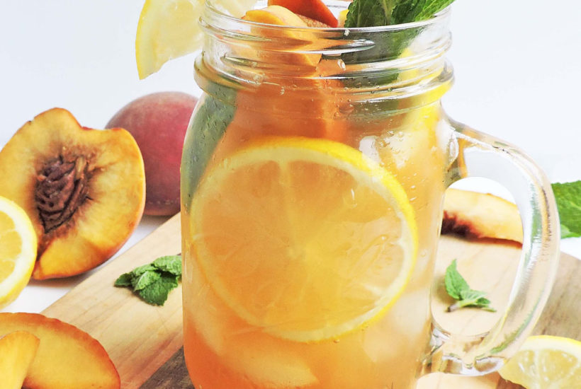 Bourbon Ginger Sweet Peach Tea in a mason jar with mint leaves, ice, lemon slices, and sliced peaches, with a striped yellow straw on a wooden board