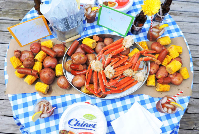 How to Throw Dad an Outdoor Crab Feast. Father's Day party idea. Crab legs, smoked sausage, red potatoes, corn on the cob, on a table with a blue checkerboard tablecloth and Chinet plates