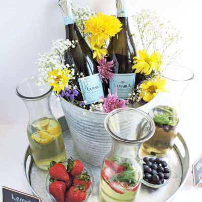 DIY Rustic Garden Party Centerpiece + Cocktail Station featuring 2 bottles of La Marca Prosecco in a tin bucket with flowers on a tin tray, surrounded my 3 glass bottles filled with Prosecco, fruit and herbs