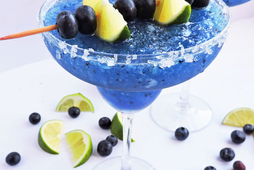 Fresh Frozen Blueberry Lime Margarita, blue margarita serve in a margarita glass with kosher salt around the rim, topped with lime wedges and blueberries