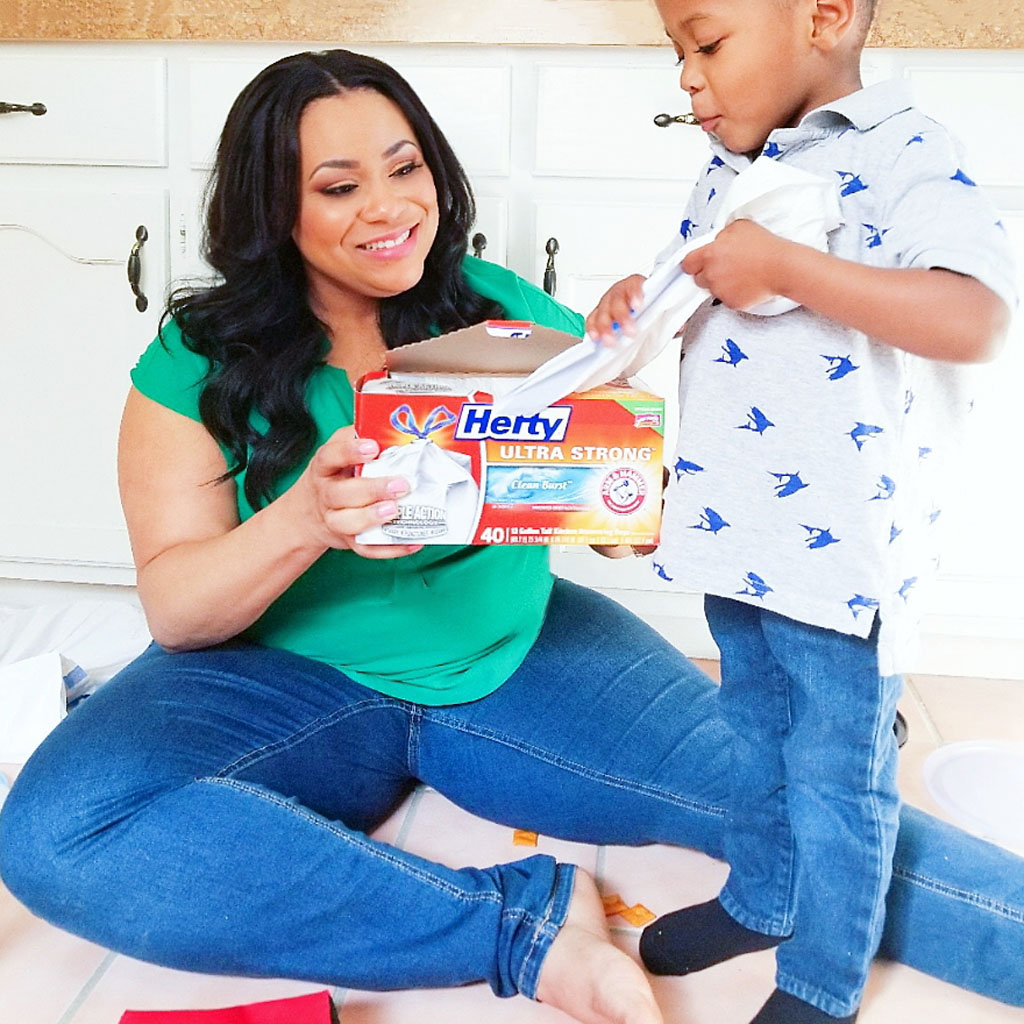 Just Call Me SuperMom-Hefty. African American (Black) mom and son laughing on kitchen floor as son grabs trash bag from Hefty trash bag box