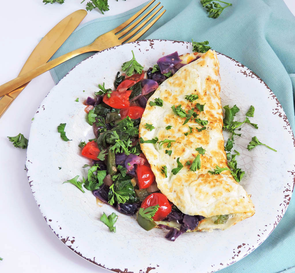Veggie Stuffed Egg White Omelet, egg white omelet stuffed with tomatoes, spinach, red cabbage, bell peppers, garlic, and mushrooms on a white plate