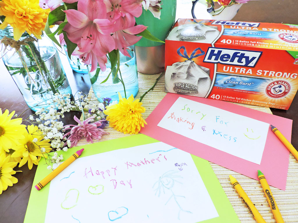 Just Call Me SuperMom-Hefty. Mother's Day cards drawn by kids on a table surrounded by a hefty trash bag box and flowers