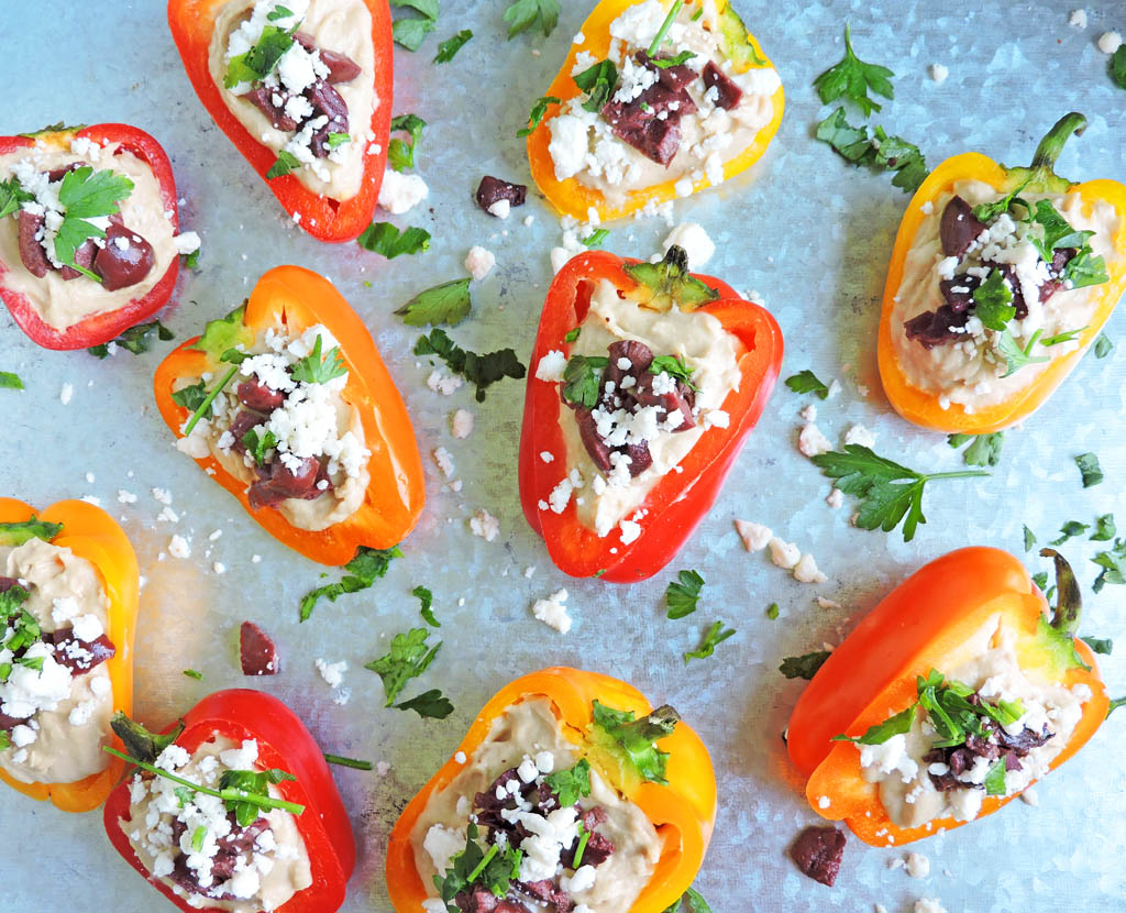 Mediterranean Hummus Stuffed Peppers-mini yellow, red, and orange bell peppers sliced in half and stuffed with hummus, topped with chopped kalamata olives, feta, and parsley