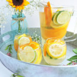 Summer Citrus White Sangria, served with slices of liime, oranges, and lemons in a glass pitcher on a galvanized serving tray