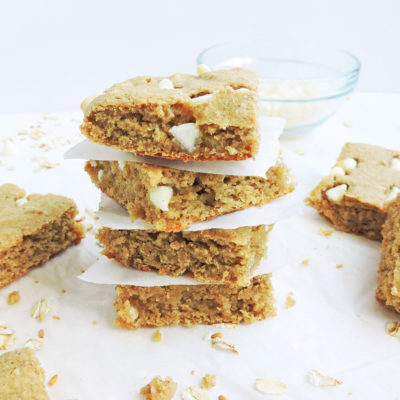 Flourless Chickpea White Chocolate Blondies- Gluten free, cut in squares, stacked on top of each other, on a white surface