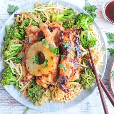 pineapple teriyaki chicken served on top of ramen noodles with broccoli and a pineapple on top. Served on a white plate with brown chopsticks
