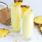 Tropical Pineapple Coconut Cooler served in a tall glass with toasted coconut around the rim, and pineapple wedge-made with Torani Syrups beautifuleatsandthings.com