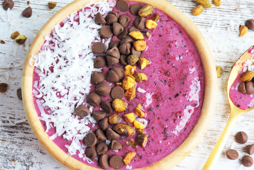 Coconut Beet Berry Smoothie Bowl- pink smoothie in a wooden bowl topped with nuts, chocolate chips and coconut,