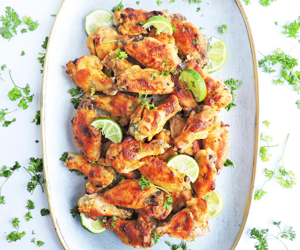 Crispy Lime Ranch Hot Wings on a silver plate with lime wedges added on top