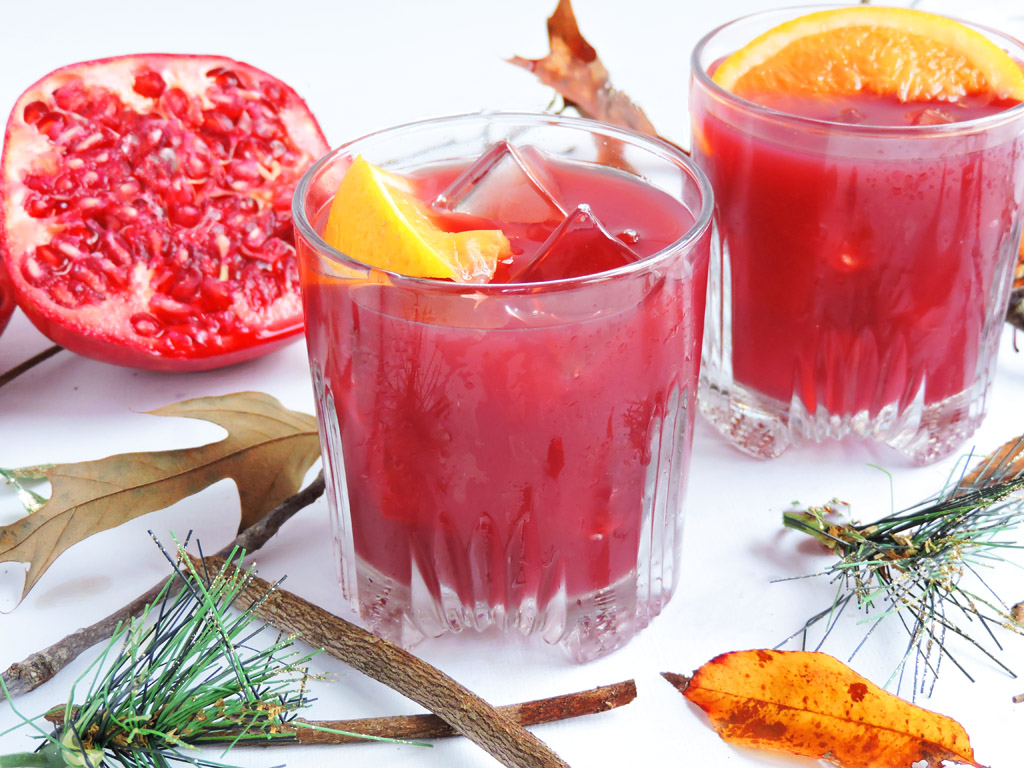 Love in the Cabin Cocktail-pomegranate, orange juice, and gin cocktail served in a glass with a orange slice on top, the perfect holiday drink