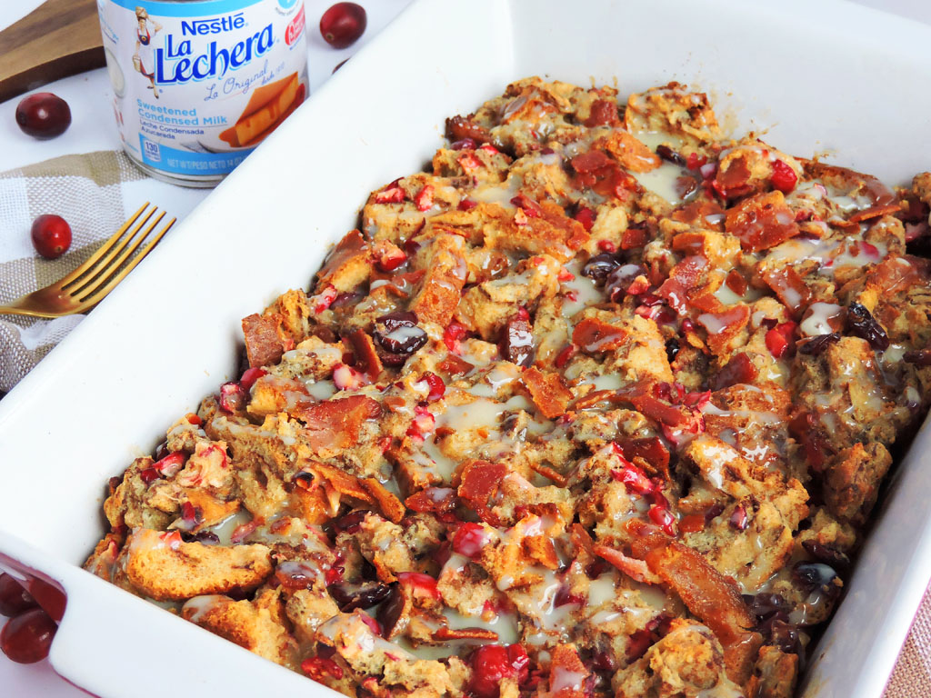 Maple Bacon Cranberry French Toast Casserole made with La Lachera and in a casserole dish with cranberries and bacon on top